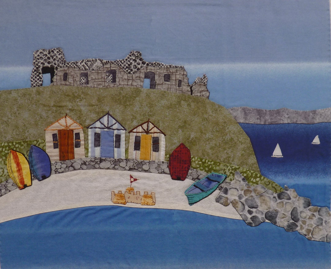 The three beach huts are constructed from my old trousers, Neil's shirt and my shirt, the yellow boat is made from a piece of my daughter's old curtain material and parts of the sand-castle are made from material that I've dyed. The little white boats are made from a white shirt of mine. Two out of three doors on the beach huts are made from material left over from my kitchen bunting.